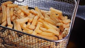 Fasi di produrre le fritture della patata Le patate fritte aspettano per essere servite in un cesto metallico archivi video