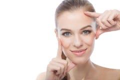 Fasion modela enmarcar su cara, sobre un fondo blanco Imagen de archivo libre de regalías