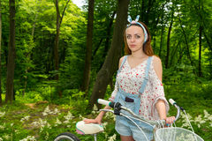 Fasionable female with her bicycle in a park. Fasionable female wearing denim overalls and a loose-fitting blouse with her bicycle in a park Stock Photos