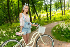 Fasionable female with her bicycle standing on a footpath in a p. Fasionable female wearing denim overalls and a loose-fitting blouse with her bicycle standing Stock Images
