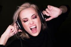 Fasionable kobieta słucha agresywna muzyka przez hełmofonów i śpiewa na gark tle Obraz Stock