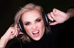 Fasionable kobieta słucha agresywna muzyka przez hełmofonów i śpiewa na gark tle Zdjęcia Stock