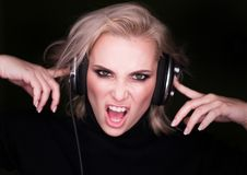 Fasionable woman listening to the agressive music via headphones and sing on gark. Fasionable woman listening to the agressive music via headphones and sing on Royalty Free Stock Image