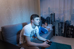 Fasionable young couple spend their free time at home. Where young men  playing a video game holding a console while his girlfriend lying on the sofa and surf Royalty Free Stock Images