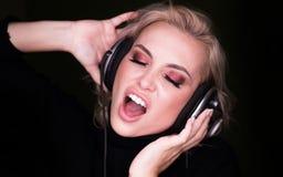 Fasionablevrouw het luisteren aan de agressieve muziek via hoofdtelefoons en zingt op garkachtergrond stock afbeelding