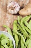 Fasolki szparagowe grula i czosnek, na drewnianym stole zdjęcie stock