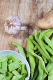 Fasolki szparagowe grula i czosnek, na drewnianym stole zdjęcia stock