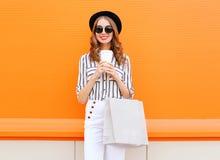 Fasonuje ładnego młodego uśmiechniętego kobieta modela z torba na zakupy trzyma filiżankę jest ubranym czarnych kapeluszy białych Fotografia Royalty Free