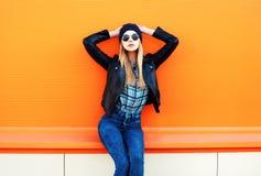 Fasonuje ładnej blondynki kobiety w rockowego czerni stylowy pozować na kolorowym pomarańczowym tle Obrazy Royalty Free