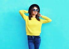 Fasonuje ładnej kobiety jest ubranym czarnego kapelusz i kolor żółty dziającego pulower nad kolorowym błękitem Obrazy Royalty Free