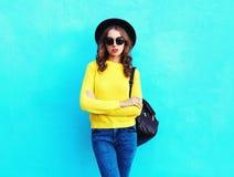 Fasonuje ładnej kobiety jest ubranym czarnego kapeluszu puloweru kolor żółty dziającego plecaka nad kolorowym błękitem Obrazy Stock