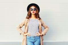 Fasonuje ładnej kobiety jest ubranym czarnych kapeluszy okulary przeciwsłonecznych nad popielatym tłem z czerwonymi wargami Fotografia Royalty Free