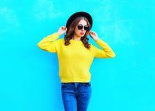 Fasonuje ładnej kobiety jest ubranym kolor żółty dziającego pulower nad kolorowym błękitem i czarnego kapelusz Zdjęcie Royalty Free