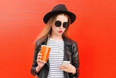 Fasonuje ładnej młodej kobiety używa smartphone w rockowym czerń stylu nad kolorową czerwienią zdjęcia royalty free