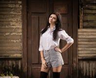 Fasonuje ładny młodej kobiety pozować plenerowy blisko starej drewnianej ściany Zdjęcia Stock
