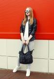 Fasonuje ładnej młodej kobiety jest ubranym rockową czarną skórzaną kurtkę, okulary przeciwsłonecznych i torbę nad czerwienią, Obraz Royalty Free