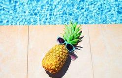 Fasonuje ananasa z okularami przeciwsłonecznymi, błękitne wody basenu tło, wakacje letni, obrazy royalty free