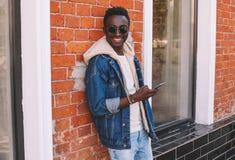 Fasonuje chłodno uśmiechniętego afrykańskiego mężczyzny z smartphone na miasto ulicie zdjęcie stock