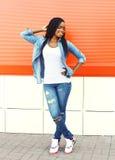 Fasonuje dosyć uśmiechać się młodej afrykańskiej kobiety w mieście nad czerwienią Zdjęcia Stock