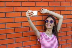 Fasonuje dosyć uśmiechać się młodej dziewczyny bierze obrazek jaźni portret na smartphone w pasiastej koszulce nad miasto czerwon Obraz Royalty Free