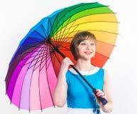 Fasonuje dosyć uśmiechać się młodej kobiety trzyma kolorowego tęcza parasol jest ubranym błękitną suknię nad białym tłem Studio s zdjęcia stock