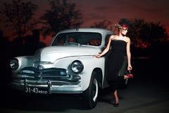 Fasonuje dziewczyny w retro stylu pozuje blisko starego samochodu zdjęcia stock