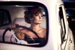 Fasonuje dziewczyny w retro stylu pozuje w starym samochodzie zdjęcie stock