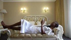 Fasonuje eleganckiego amerykanina afrykańskiego pochodzenia trybu kłamstwo przy żakietem i zabawę z surfować internet zdjęcie wideo
