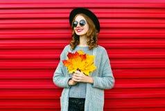 Fasonuje jesień portreta uśmiechniętej kobiety z żółtymi liśćmi klonowymi Zdjęcia Royalty Free