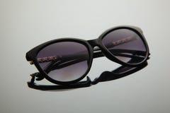 Fasonuje kobieta okulary przeciwsłonecznych, czarny klingeryt, złocista dekoracja na douche, elegancki gradient z polaryzacyjnym  obraz royalty free