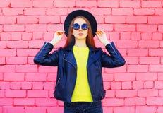 Fasonuje kobiety jest ubranym kolor żółty dziającego sweate rjacket nad kolorowymi różowymi cegłami i czarnego kapelusz Zdjęcie Royalty Free