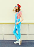 Fasonuje młodej ładnej kobiety jest ubranym drelichowego kombinezon w profilu nad bielem Zdjęcia Stock