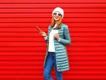 Fasonuje młodej uśmiechniętej kobiety używa smartphone z filiżanką obraz stock