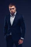 Fasonuje młodego biznesmena czerni kostium na ciemnym tle Fotografia Stock
