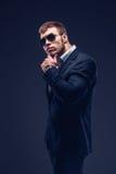 Fasonuje młodego biznesmena czerni kostium na ciemnym tle Fotografia Royalty Free