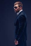 Fasonuje młodego biznesmena czerni kostium na ciemnym tle Obrazy Stock