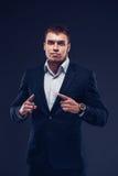 Fasonuje młodego biznesmena czerni kostium na ciemnym tle Obrazy Royalty Free