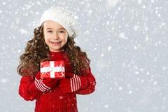 Fasonuje małej dziewczynki z Bożenarodzeniowym prezentem na śnieżnym tle, Fotografia Stock