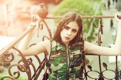 fasonuje makeup Ładna dziewczyna trzyma kruszcowego balkon w kamuflaż kamizelce ostro protestować zdjęcie royalty free
