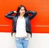 Fasonuje pięknej młodej kobiety jest ubranym rockową czarną kurtkę nad czerwienią Zdjęcie Stock