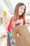 Fasonuje pomyślnej kobiety trzyma kredytową kartę i torby, zakupy centrum handlowe Fotografia Royalty Free