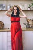 Fasonuje portret atrakcyjna elegancka ciężarna dama w długim czerwonym sarafan i słomianym kapeluszu, fotografia piękny i szczęśl zdjęcia royalty free