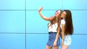 Fasonuje portret dwa modnisiów dosyć ono uśmiecha się kobieta trzyma smartphone i robi selfie przeciw w okularach przeciwsłoneczn zdjęcie wideo