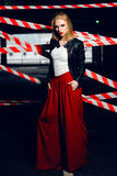 Fasonuje portret seksowna blondynki dziewczyna jest ubranym rockowego czerni stylowy pozować na tle ostrzegawcza taśma z czerwony fotografia royalty free