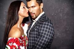 Fasonuje przystojnego eleganckiego mężczyzna w kostiumu z piękną seksowną kobietą pozuje blisko szarości ściany obraz stock