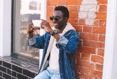 Fasonuje rozochoconego uśmiechniętego afrykańskiego mężczyzny bierze selfie smartphone lub ma wideo wezwanie zdjęcie royalty free