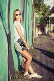 Fasonuje styl życia, Piękna młoda blondynki kobieta z deskorolka zdjęcie royalty free