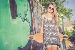 Fasonuje styl życia, Piękna młoda blondynki kobieta z deskorolka zdjęcie stock