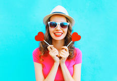 Fasonuje szczęśliwej uśmiechniętej kobiety z dwa czerwieni lizaka kształtem serce nad kolorowym fotografia stock