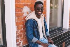 Fasonuje uśmiechniętego afrykańskiego mężczyzny w cajgach kurtka siedzi na miasto ulicie obraz royalty free
